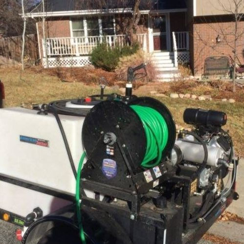 A Picture of a Hydro Jetter Outside a House.